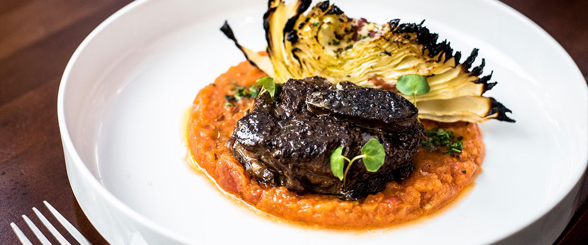 Smoked & Braised Beef Short Ribs with Coal-Roasted Cabbage and Smoked Tomatoes on white plate with fork.