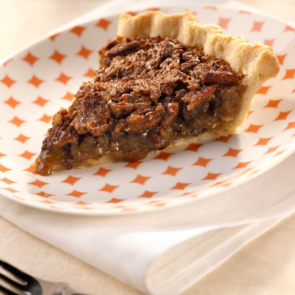 Chocolate Bourbon Pecan Pie on a decorative plate and white towel.