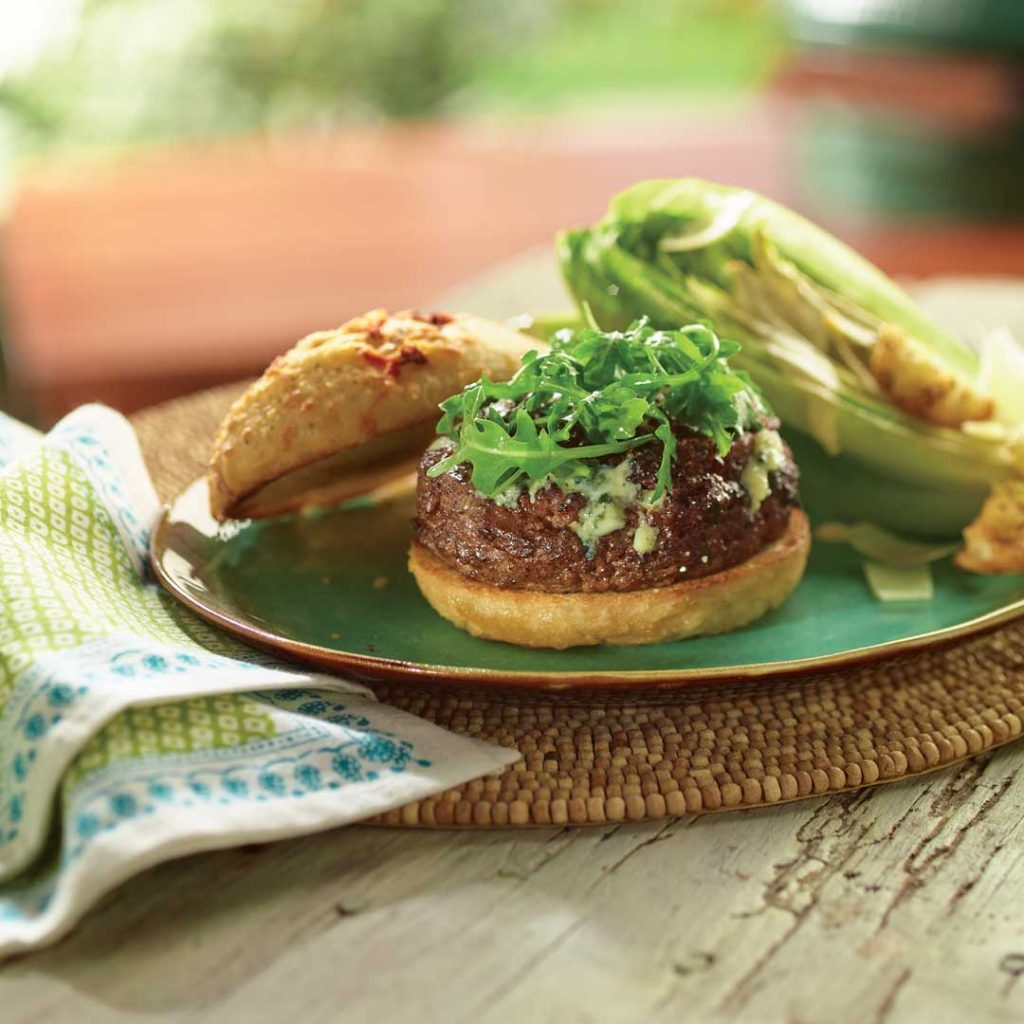 Wild Mushroom and Blue Cheese Stuffed Burger on a green plate placed on a table with a towel and woven place mat.