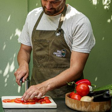 Man Slicing Tomatoes with Big Green Egg Apron on