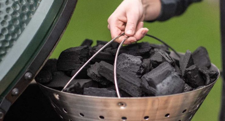 Man with Fire Bowl filled with charcoal putting it into the EGG